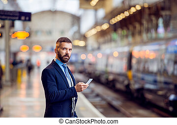 Hipster businessman with smartphone, waiting, train platform