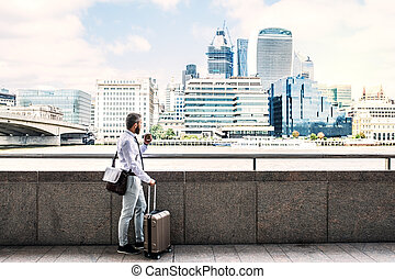 Hipster businessman with suitcase standing by the river in London.