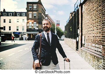 Hipster businessman with suitcase walking down the street in London.