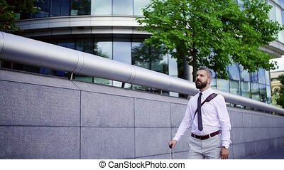 Hipster businessman with suitcase walking down the street in...