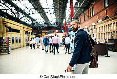 Hipster businessman with suitcase walking inside subway station in London.