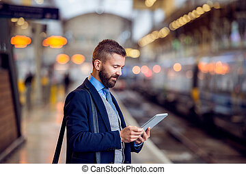 Hipster businessman with tablet, waiting, train platform