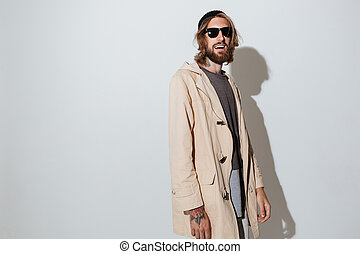 Hipster cheerful man wearing sunglasses standing isolated