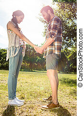 Hipster couple holding hands in park