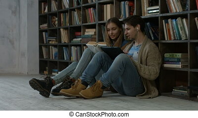 Hipster couple learning together in the library