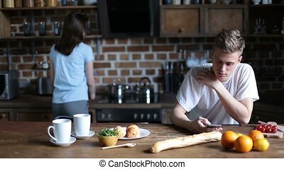 Hipster couple relaxing in the kitchen in morning