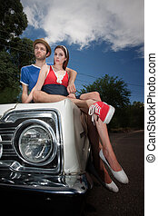 Hipster Couple Sitting on an Old Car