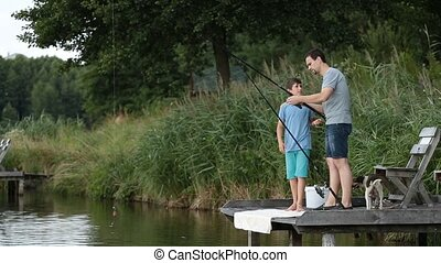 Hipster dad and boy enjoying fishing at the pond