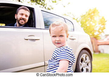 Hipster father in the car and his little daughter