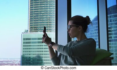 Hipster female in glasses is using apps on her mobile phone and taking photos of skyscrapers view. Woman with smartphone