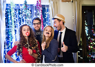 Hipster friends celebrating New Years Eve together,...