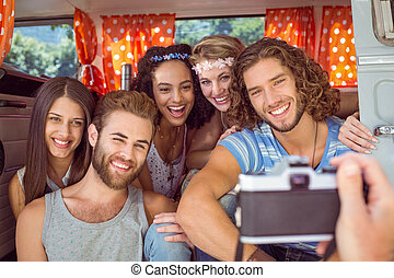 Hipster friends in a camper van on a summers day