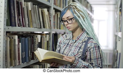 Hipster girl absorbed in reading book in library