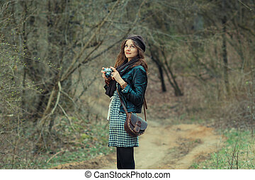Lovely Hipster Girl Filming In The Woods On A Vintage Movie Camera