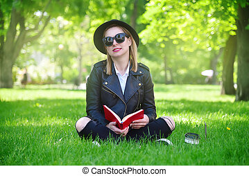 girl in hat sitting on grass