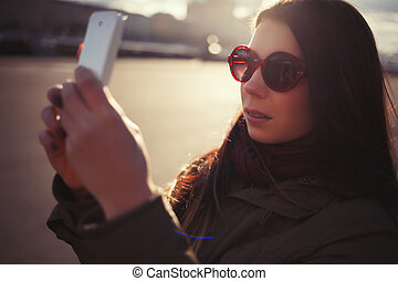 Hipster girl in sunglasses taking photo with smart phone