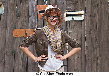 Hipster girl posing at wooden background