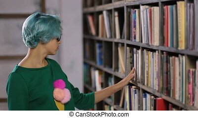 Hipster girl searching for book in a bookstore