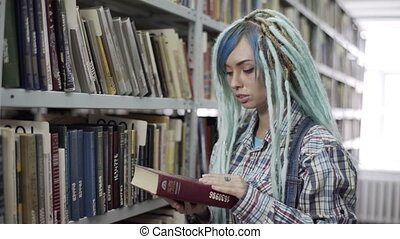 Hipster girl searching for book in a bookstore - Portrait of...
