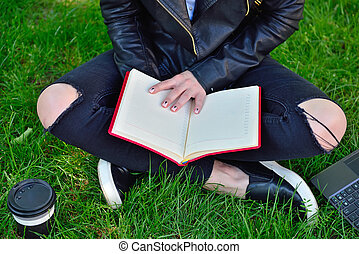 girl sitting on grass and reading book