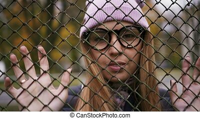 Hipster girl stands near a fence and looks at the camera.