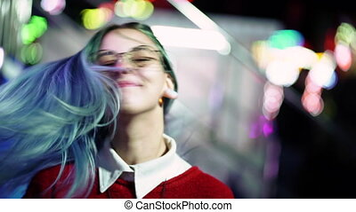 Hipster girl waving head in different directions, playing with dyed blue hair. Woman with nose piercing, transparent glasses, ears tunnels, unusual hairstyle in amusement park.