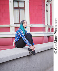 Hipster girl with blue dyed hair. Woman with piercing in nose, ears tunnels and unusual hairstyle having fun, posing in European city. Carefree concept.