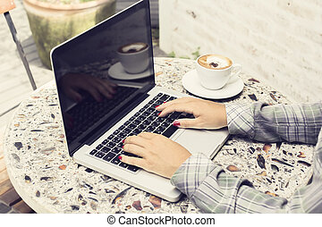 Hipster girl with laptop, cup of coffee on the table outdoor