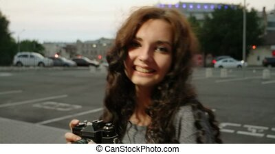Hipster girl with vintage camera smiling in the street -...
