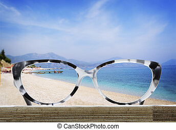 glasses on a wooden table in front of the sea