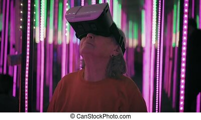 Hipster grandmother is standing in neon lights using virtual...