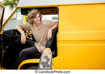 guy sitting wheel of rented car during his anticipated travel on summer vacations