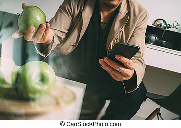 hipster hand using smart phone for mobile payments online business, sitting on sofa in living room, holding green apples in wooden tray,