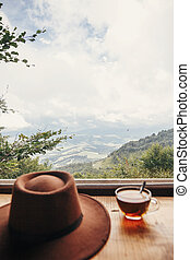 hipster hat and tea in glass on wooden table at window light with view on mountains and sky. delicious hot drink on mountain top. summer travel and wanderlust. focus on mountain