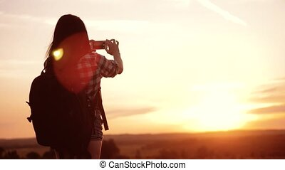 Hipster hiker lifestyle silhouette girl is shooting video of...
