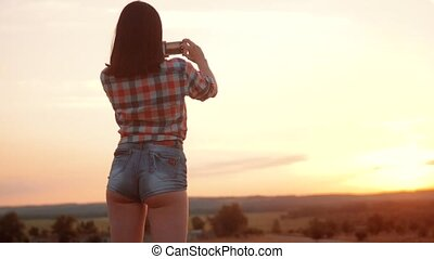 Hipster hiker silhouette girl is shooting video lifestyle of...