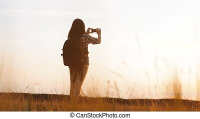 Hipster hiker silhouette girl is shooting video of beautiful nature sundown on cell telephone smartphone slow motion video. Female tourist is taking photo with mobile phone camera. female girl tourist travel lifestyle concept