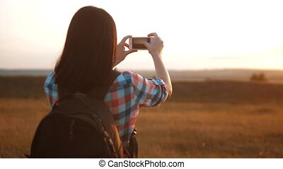 Hipster hiker silhouette girl is shooting video of beautiful...