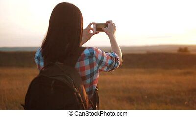 Hipster hiker silhouette girl is shooting video of beautiful nature sundown on cell telephone smartphone slow motion video. Female tourist is taking photo with mobile phone camera. girl lifestyle tourist travel concept