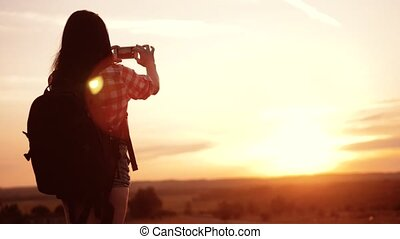Hipster hiker silhouette lifestyle girl is shooting video of...