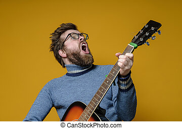 Hipster in an old sweater plays an acoustic guitar and sings...