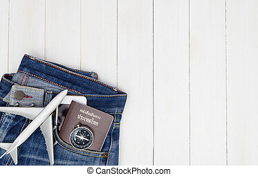 Hipster Jean pant with travel objects on white wooden copy space