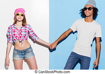 Hipster love. Funky young couple wearing sunglasses and smiling while standing against colorful background