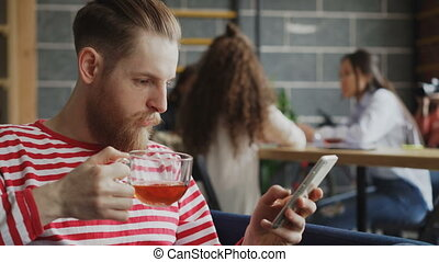 Hipster male entrepreneur surfing smarpthone and drinking tea while having break in busy office