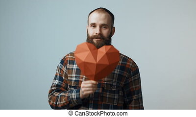 Hipster man holding heart shape in hand - Bearded hipster...