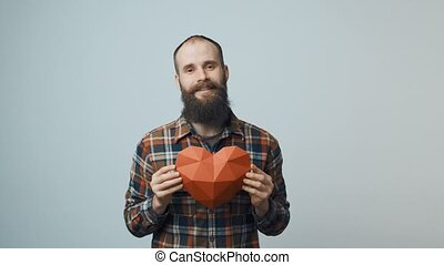 Hipster man holding heart shape in hands - Bearded hipster...