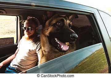Hipster Man in glasses and Dog sitting in a car Outdoor Lifestyle Travel Friendship concept nature on background
