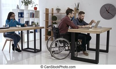 Hipster man in wheelchair working in office