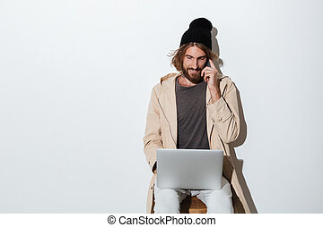 Hipster man looking aside with laptop computer