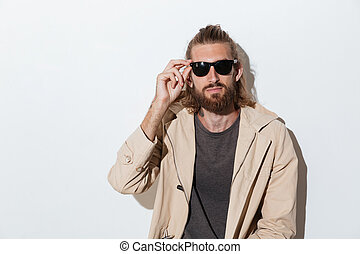Hipster man looking camera isolated over wall background.